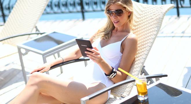 Девушка читает PocketBook, лежа на шезлонге