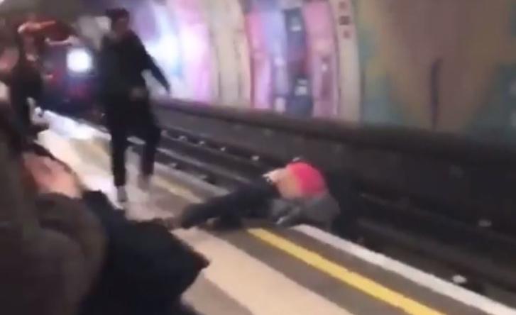 Фото №1 - Два идиота затеяли драку понарошку, а на рельсы перед мчащимся поездом упали по-настоящему! (ВИДЕО)
