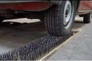 Автойога: легковушка катит по 5000 гвоздей, вбитых в доски (видео)