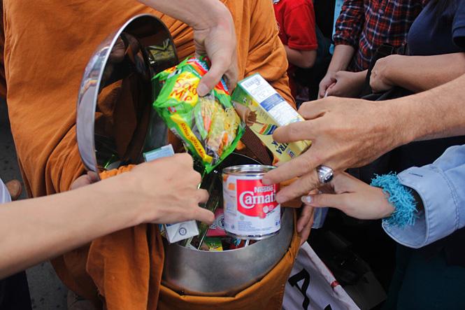 Буддийский монах получает в качестве подношений еду и деньги