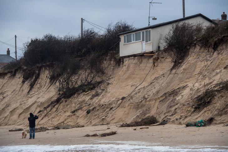 Фото №1 - Дома зависли над обрывом после того, как берег смыло в море!