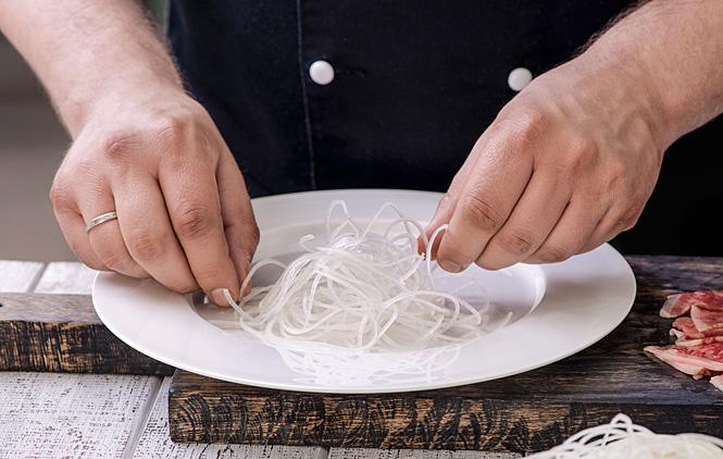 Скрасивой небрежностью урони дайкон на дно тарелки