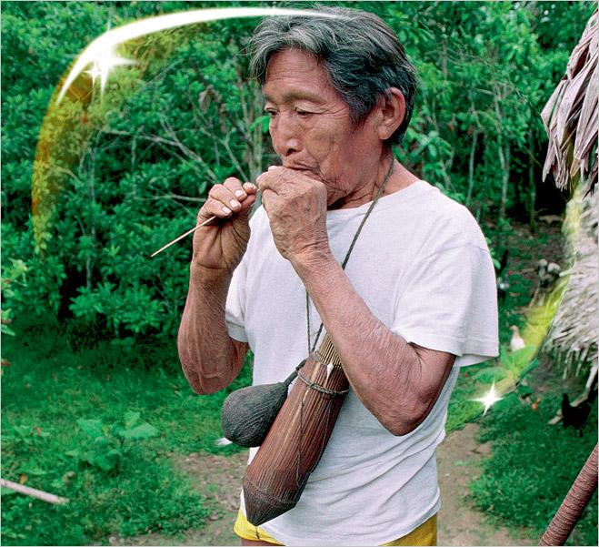 Амазонский индеец племени ягуа с духовой трубкой во рту