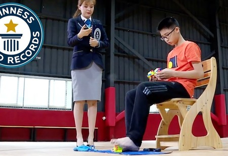 Новый рекорд: подросток собрал три кубика Рубика одновременно, причём один из них — ногами (видео)