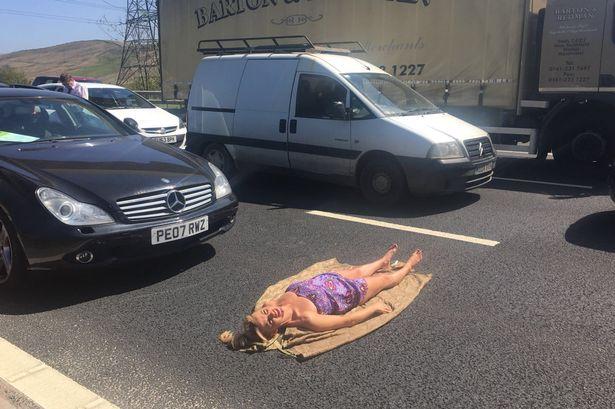 Фото №3 - Полуголая девушка загорает в пробке! В прямом смысле слова: лежа прямо на дороге!