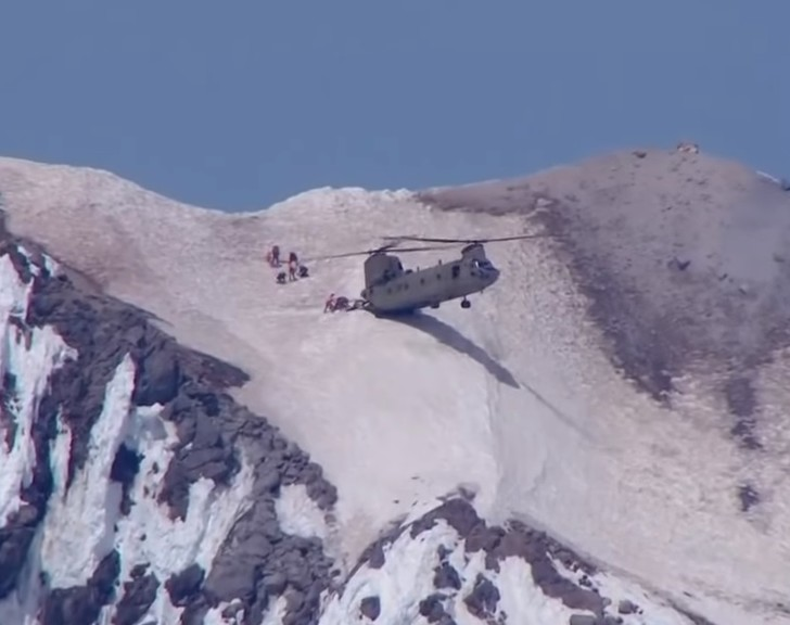 Фото №1 - Безумное ВИДЕО: тяжелый вертолет вплотную подлетает к склону, чтобы спасти 6 спасателей и 1 идиота