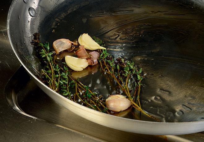 Положить на сковородку с подсолнечным маслом, чесноком и веточками тимьяна