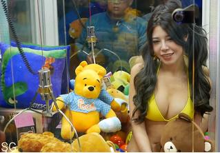 Видео: девушка в бикини в автомате для вытягивания плюшевых игрушек