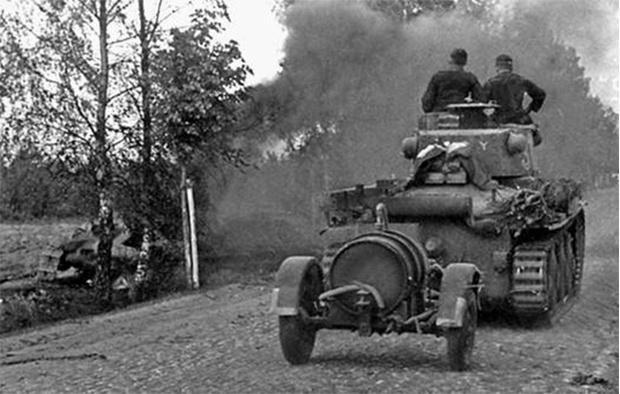 Немецкий танк PzKpfw38(t) едет мимо горящего советского танка. На буксире у «чеха» – бочка с горючим. Район Алитуса